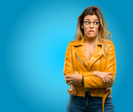 Beautiful young woman nervous and scared biting lips looking camera with impatient expression, pensive, blue background Stock Photo
