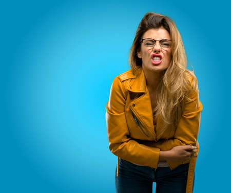 Beautiful young woman angry and stressful frowns face in dissatisfaction, irritated and annoyed, expressing anger, blue background