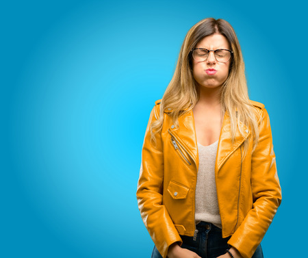Beautiful young woman puffing out cheeks, having fun making funny face, blue background