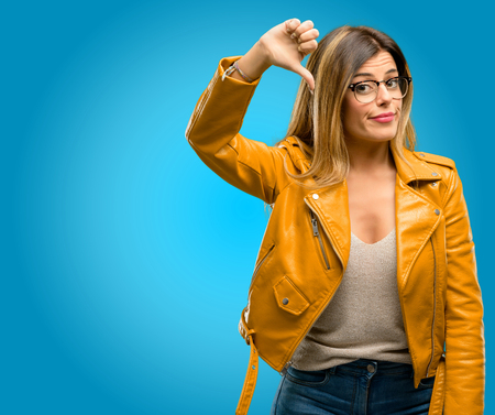 Beautiful young woman showing thumbs down unhappy sign of dislike, negative expression and disapproval, blue background