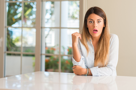 Young beautiful woman at home scared in shock, expressing panic and fear