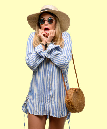 Young woman wearing sunglasses and summer hat terrified and nervous expressing anxiety and panic gesture, overwhelmed