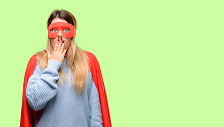 Young super woman covers mouth in shock, looks shy, expressing silence and mistake concepts, scared Stock Photo