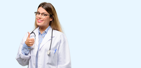 Young doctor woman, medical professional smiling broadly showing thumbs up gesture to camera, expression of like and approval Stock Photo