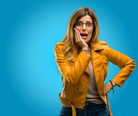 Beautiful young woman scared in shock, expressing panic and fear, blue background Foto de archivo