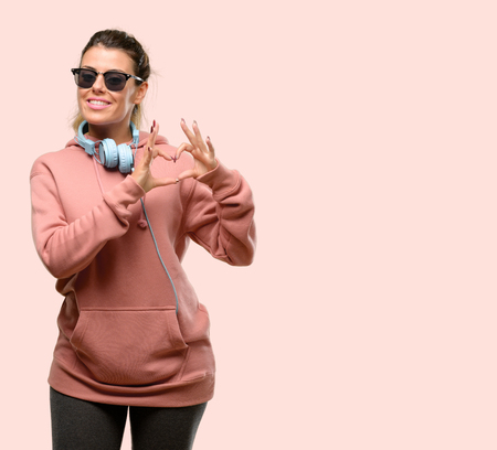 Young sport woman with headphones and sunglasses annoyed with bad attitude making stop sign with hand, saying no, expressing security, defense or restriction, maybe pushing Foto de archivo