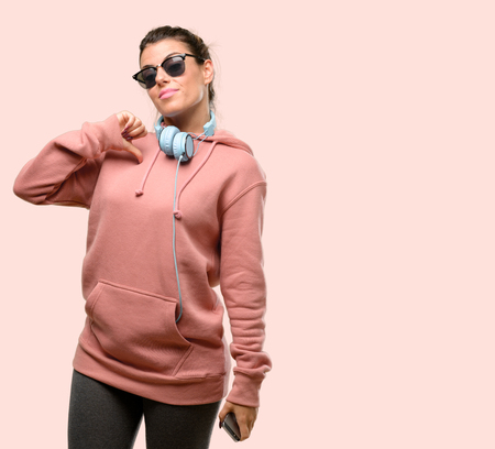 Young sport woman with headphones and sunglasses irritated and angry expressing negative emotion, annoyed with someone