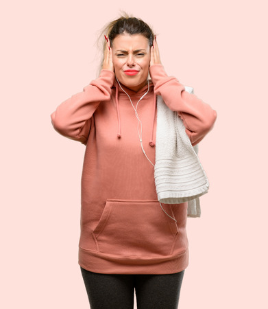 Young sport woman wearing workout sweatshirt covering ears ignoring annoying loud noise, plugs ears to avoid hearing sound. Noisy music is a problem. Reklamní fotografie