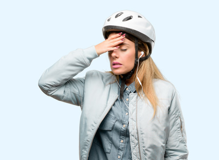 Young woman with bike helmet and earphones terrified and nervous expressing anxiety and panic gesture, overwhelmed