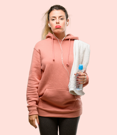 Young sport woman wearing workout sweatshirt with sleepy expression, being overworked and tired Stock Photo