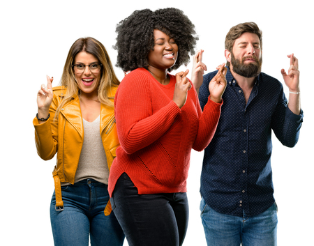 Group of three young men and women with crossed fingers asking for good luck