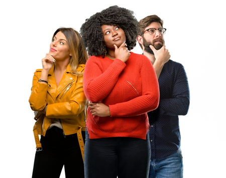Group of three young men and women thinking and looking up expressing doubt and wonder Stock Photo