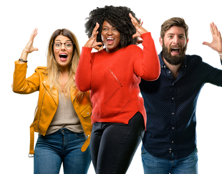 Group of three young men and women happy and surprised cheering expressing wow gesture Stock Photo