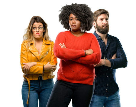 Group of three young men and women nervous and scared biting lips looking camera with impatient expression, pensive Stock Photo