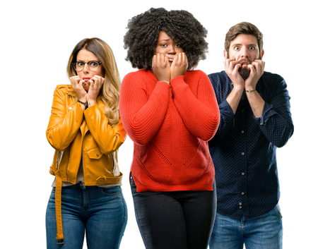 Group of three young men and women terrified and nervous expressing anxiety and panic gesture, overwhelmed Stock Photo