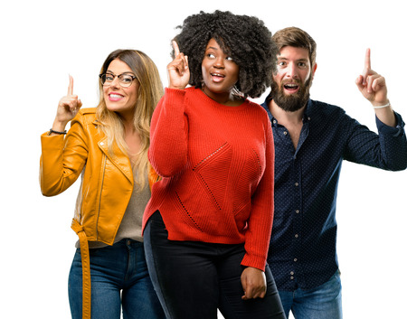 Group of three young men and women happy and surprised cheering expressing wow gesture pointing up Stock Photo