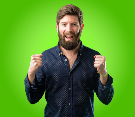 Young hipster man with big beard happy and excited expressing winning gesture. Successful and celebrating victory, triumphant over green background