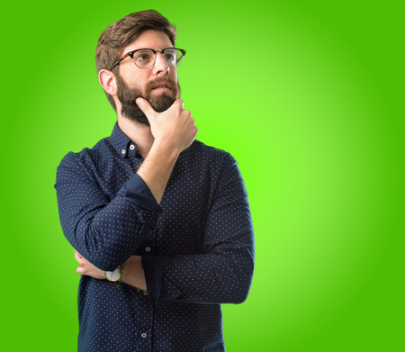 Young hipster man with big beard thinking and looking up expressing doubt and wonder over green background