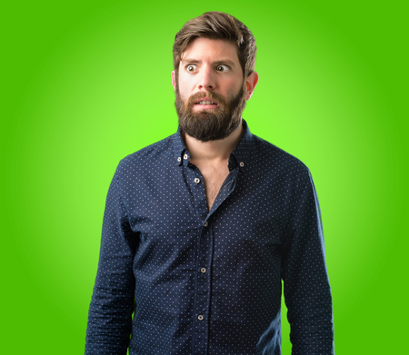 Young hipster man with big beard making funny face fooling over green background