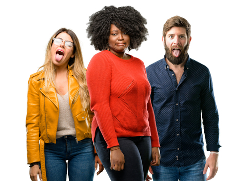 Group of three young men and women feeling disgusted with tongue out