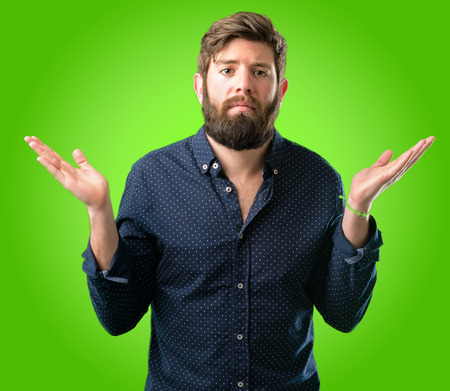 Young hipster man with big beard doubt expression, confuse and wonder concept, uncertain future over green background Stock Photo