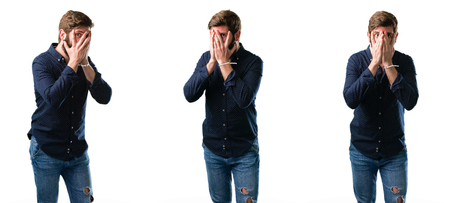 Young man with beard smiling having shy look peeking through her fingers, covering face with hands looking confusedly broadly isolated over white background Stock Photo