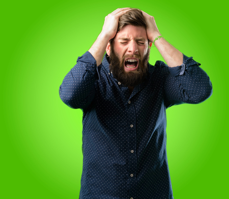 Young hipster man with big beard terrified and nervous expressing anxiety and panic gesture, overwhelmed over green background Stock Photo