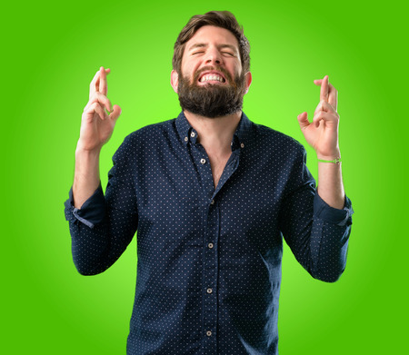 Young hipster man with big beard with crossed fingers asking for good luck over green background Stock Photo