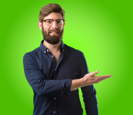 Young hipster man with big beard holding something in his empty hand over green background