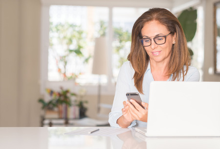 Middle age woman using smartphone and laptop, indoor Standard-Bild