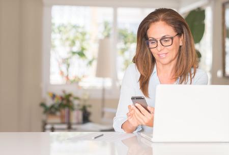 Mujer de mediana edad con smartphone y portátil, interior Foto de archivo
