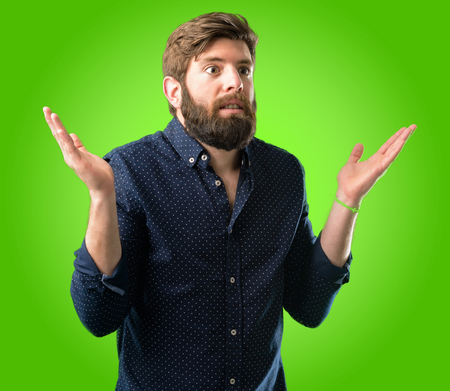 Young hipster man with big beard doubt expression, confuse and wonder concept, uncertain future shrugging shoulders over green background