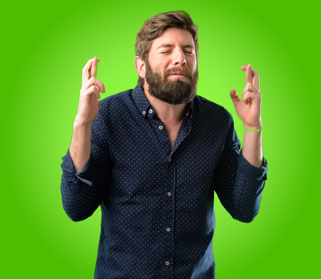 Young hipster man with big beard with crossed fingers asking for good luck over green background Banque d'images - 104066784