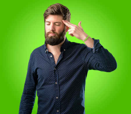 Young hipster man with big beard unhappy making suicide gesture, tired of everything. Shoots with his hand imitating gun, upset over green background