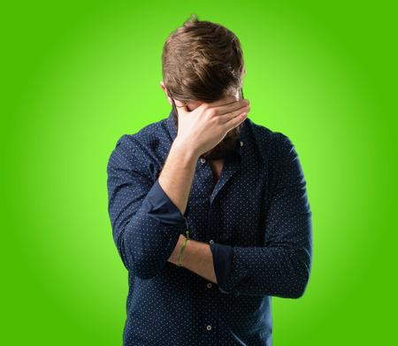 Young hipster man with big beard stressful keeping hands on head, tired and frustrated over green background