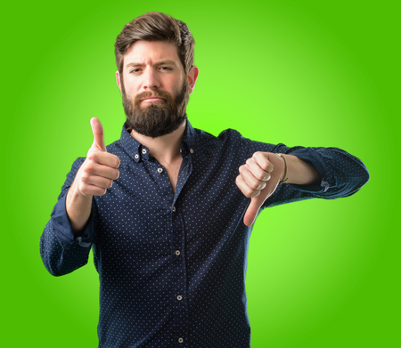 Young hipster man with big beard confused with thumbs up and down, trying to take a decision expressing doubt and frustration over green background