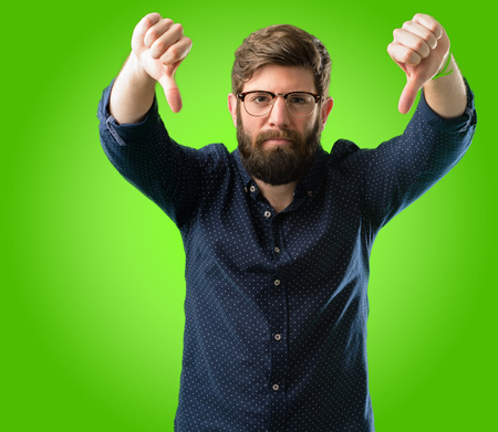 Young hipster man with big beard showing thumbs down unhappy sign of dislike, negative expression and disapproval over green background