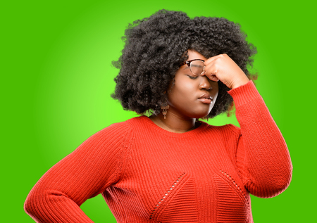 Beautiful african woman with sleepy expression, being overworked and tired, rubbes nose because of weariness Stock Photo