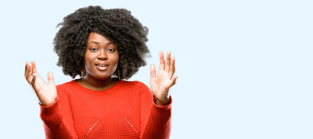 Beautiful african woman confident and happy with a big natural smile welcome gesture, blue background