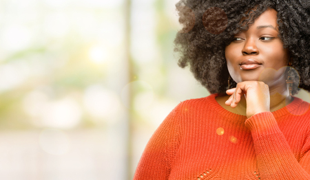 Beautiful african woman thinking thoughtful with smart face, expressing question and doubt. Imagine the solution, outdoor Stock Photo