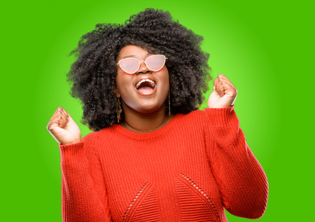 Beautiful african woman happy and excited expressing winning gesture. Successful and celebrating victory, triumphant Stock Photo