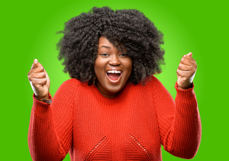 Beautiful african woman happy and surprised cheering expressing wow gesture