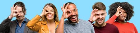 Groep gemengde mensen, vrouwen en mannen die camera door vingers in ok gebaar bekijken. Imiterende verrekijker, mooie ogen en glimlach