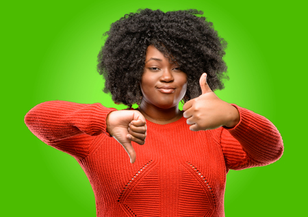 Beautiful african woman confused with thumbs up and down, trying to take a decision expressing doubt and frustration