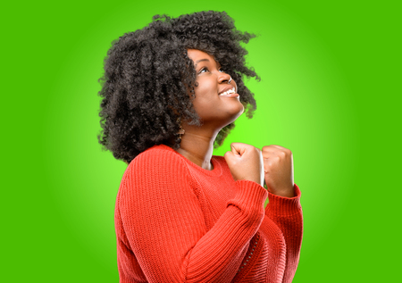 Beautiful african woman happy and excited celebrating victory expressing big success, power, energy and positive emotions. Celebrates new job joyful Stock Photo