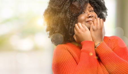 Beautiful african woman terrified and nervous expressing anxiety and panic gesture, overwhelmed, outdoor Stock Photo