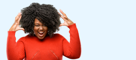 Beautiful african woman happy and surprised cheering expressing wow gesture, blue background Archivio Fotografico