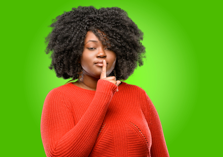 Beautiful african woman with index finger on lips, ask to be quiet. Silence and secret concept 免版税图像