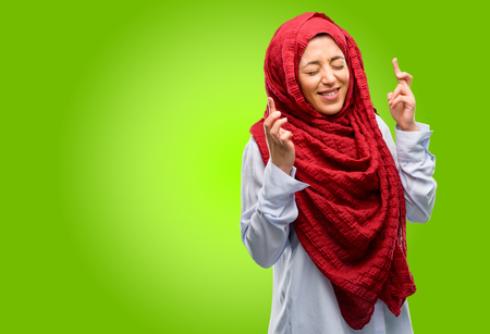 Young arab woman wearing hijab with crossed fingers asking for good luck