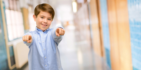 Handsome toddler child with green eyes pointing to the front with finger at school corridor